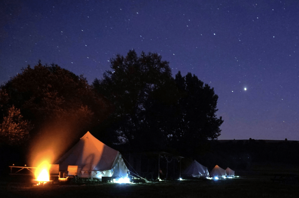 Bell tents lit up under the night sky